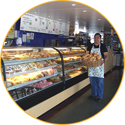 Bakery With Worker Holding Basket Of Fresh Bread